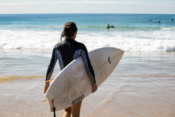 A surfer with surfboard looking toward the surf
