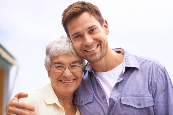 Young man and older woman cuddling and smiling