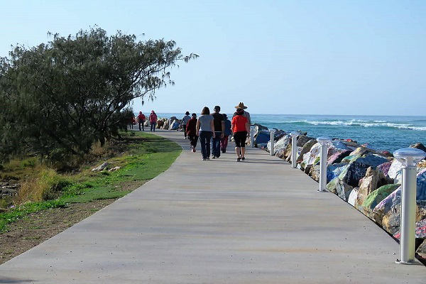 A group of walkers on a wide path near ocean