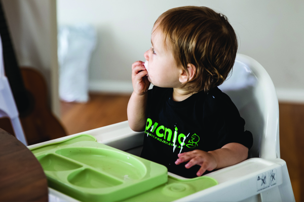 Child eating food in a high chair