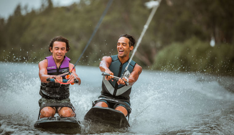 Two people wakeboarding