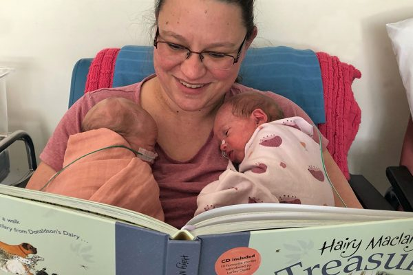 woman reading to new-born twins