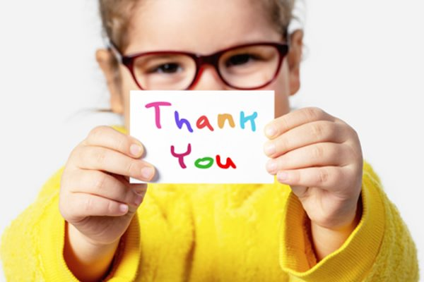 Child holding thank you card