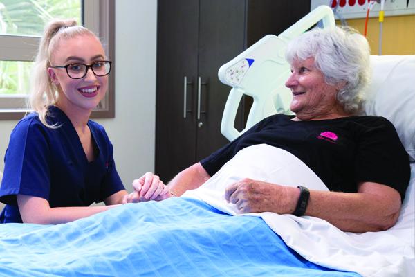 Nurse holding a patient's hand smiling